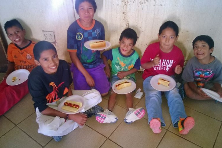 Kids eating hot dogs, nachos and juice after service.